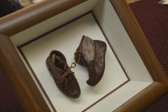 Ensiaskel kengät vitriinikehyksessä